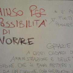 Un cartello affisso su un locale chiuso di via Lagalante