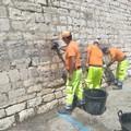 Grandi pulizie a Porta Vassalla, rimosse erbacce e scritta dal muraglione