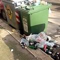 Raccolta del vetro, bidoni pieni e rifiuti per strada