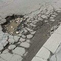 La buca si trasforma in enorme pozzanghera: fango e detriti contro la vetrina del negozio