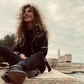 """Nina de  """"Le Iene """" sorride dal muretto della villa comunale di Trani: sarà per diletto o una inchiesta?"""