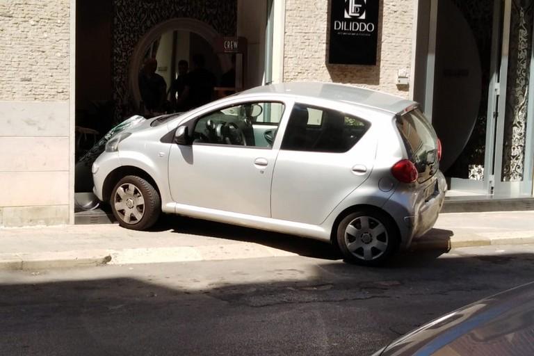 Auto contro vetrina di un'attività commerciale